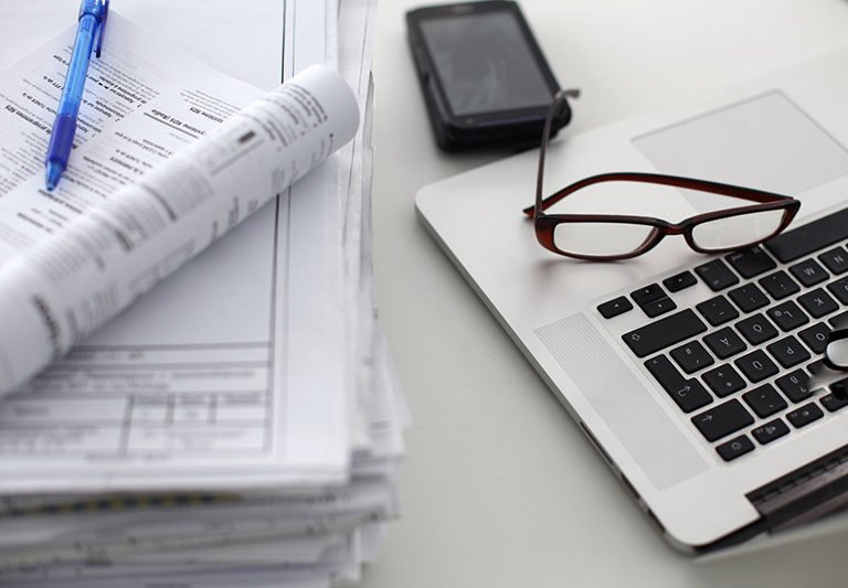 Banker's desk that contains a stack of documents, a computer, and smartphone