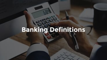 """Banker that is seated at a modern desk and using a calculator with text, """"Banking definitions"""""""
