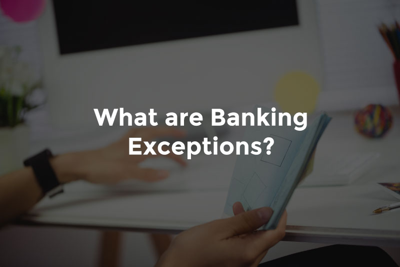 """Banker's hand typing while reading notebook in other with text, """"What are banking exceptions"""""""
