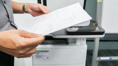 Banker who is holding a document and is standing next to a scanner