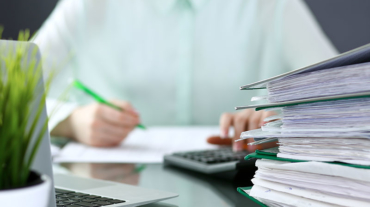 Banker processing paper reports with big stack of paperwork