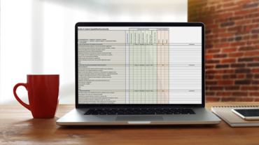 Banker's desk with a red coffee mug, notebook, mobile device, and laptop with the imaging impact spreadsheet