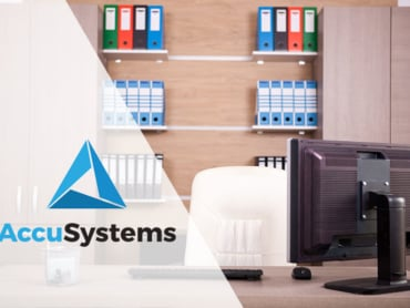 Banker's desk with shelving filled with reports and AccuSystems logo