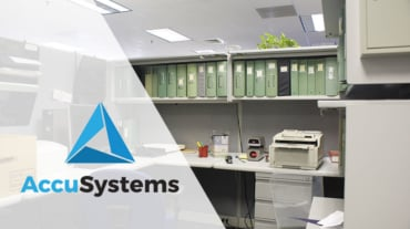 Banker's cubicle with reports and scanner and AccuSystems logo