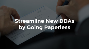 """Hand signing bank deposit slip with text, """"Streamline new DDAs by going paperless"""""""